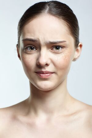 Emotional young woman face portrait with displeasure facial expression. Human female natural emotions and expressions concept. Girl with clean, healthy skin and nude makeup posing on white background. Banco de Imagens