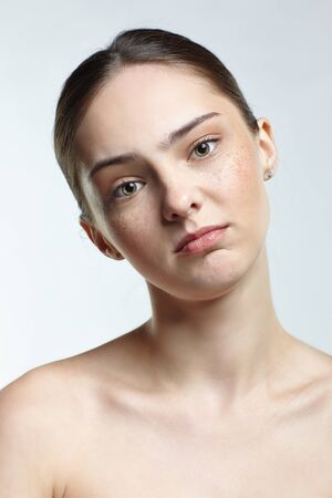 Emotional young woman face portrait with calm and tender facial expression. Human female natural emotions and expressions concept. Girl with clean, healthy skin and makeup on white background.