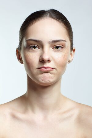 Emotional young woman face portrait with offended facial expression. Human female natural emotions and expressions concept. Girl with clean, healthy skin and nude makeup posing on white background.