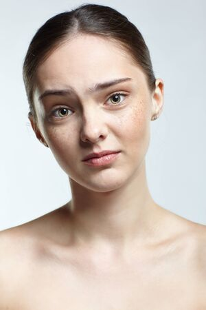 Emotional young woman face portrait with regretful, facial expression. Human female natural emotions and expressions concept. Girl with clean, healthy skin and nude makeup posing on white background.