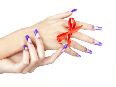 Hands with blue french acrylic nails manicure and painting with red bow on finger isolated white background 免版税图像 - 151043232