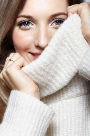 Blonde young beautiful woman dressed in large white woolen sweater on gray background. Female with hands near face. Girl covers her face with a collar. 免版税图像 - 151018965