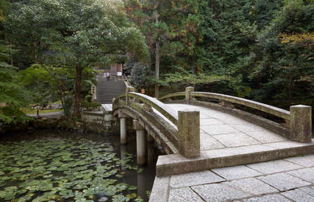 The view of the stone arch bridge over the pond with water lilies in the Yuzen'en garden at Chion-in temple complex. Kyoto. Japan 免版税图像 - 155686271