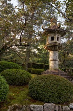 The view of the traditional pedestal Kasuga-doro stone lantern in the garden of the central Kyoto. Japan 免版税图像 - 155686276