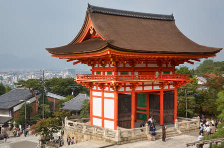 Kyoto, Japan - November 23, 2007: The view of two-story Nio-mon (Deva Gate), the main entrance to Kiyomizu-dera Temple, on the background of the old town of Kyoto. Japan