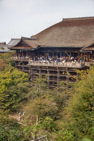 Kyoto, Japan - November 23, 2007: The large wooden stage in the main hall of Kiyomizu-dera temple which rises on the wooden pillars above the bright green vegetation of the hill. Kyoto. Japan 免版税图像 - 154913650