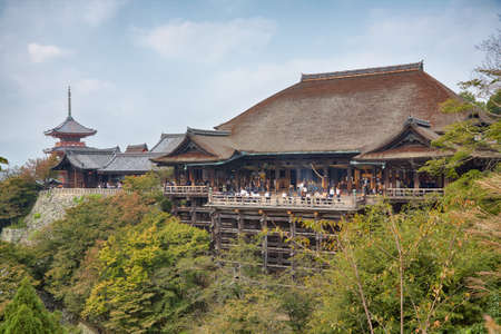 Kyoto, Japan - November 23, 2007: The large wooden stage in the main hall of Kiyomizu-dera temple which rises on the wooden pillars above the bright green vegetation of the hill. Kyoto. Japan 免版税图像 - 154913652