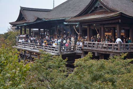 Kyoto, Japan - November 23, 2007: The large wooden stage in the main hall of Kiyomizu-dera temple which rises on the wooden pillars above the bright green vegetation of the hill. Kyoto. Japan 免版税图像 - 154913653