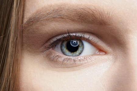 Closeup macro shot of human female eye. Woman with natural face beauty makeup.