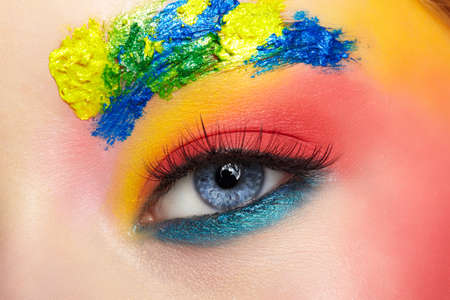 Close-up macro shot of teenager girl eye with unusual art make-up. Female face painting on brows and around eye. 免版税图像