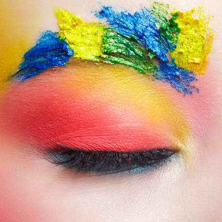 Close-up macro shot of closed teenager female eye with unusual art make-up and face painting on brows and around eye.
