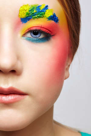 Close-up teenager girl half face portrait with unusual face art make-up. Paint on brows and hair. 免版税图像