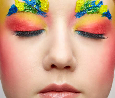 Close-up female portrait with unusual face art make-up with paint on brows. Eyes closed. 免版税图像
