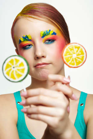 Teenager girl with unusual face art make-up. Child trying to choose between two lollipops. Sweet tooth concept.