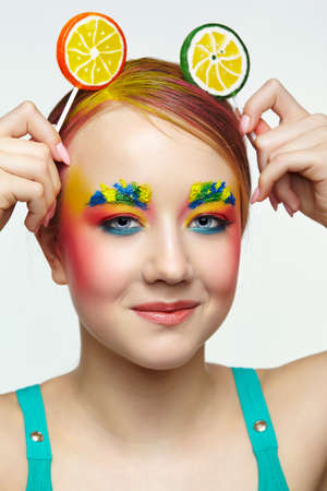 Teenager girl with unusual face art make-up. Child with lollipops in hands on head like ears. Sweet tooth concept.