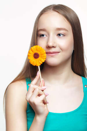 Smiling teenager girl with flower lollipop in hands. Sweet tooth concept. 免版税图像