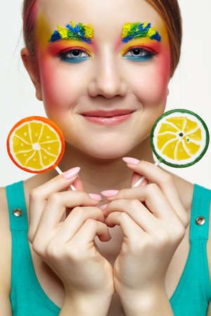 Teenager girl with unusual face art make-up. Child with lollipops in hands. Sweet tooth concept.