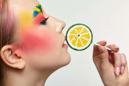 Teenager girl with unusual face art make-up. Child with lollipops in hands near mouth. Sweet tooth concept.