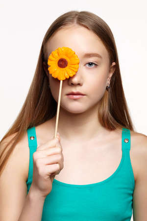Teenager girl with with flower lollipop in hands closing eye. Sweet tooth concept.