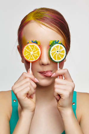 Teenager girl with unusual face art make-up show tongue. Child with lollipops in hands closing eyes. Sweet tooth concept. 免版税图像
