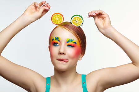 Teenager girl with unusual face art make-up show tongue. Child with lollipops in hands on head like ears. Sweet tooth concept.
