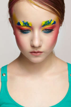Close-up teenager girl face portrait with unusual face art make-up. Paint on brows and hair. 免版税图像