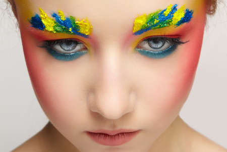 Close-up teenager girl face portrait with unusual face art make-up. Paint on brows. 免版税图像