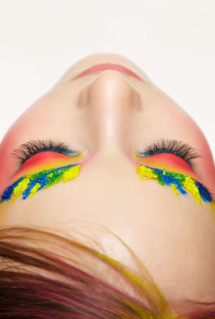 Close-up teenager girl face portrait with unusual face art make-up. Paint on brows and hair. Female with eyes closed. 免版税图像