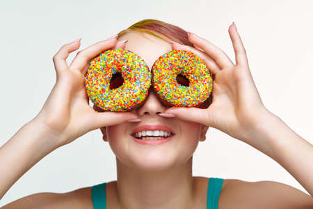 Teenager girl with unusual face art make-up. Child with donuts in hands closing eyes and looking through holes in donuts and smiling. Sweet tooth concept.