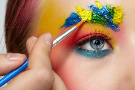 Female portrait with unusual face art makeup. Paint on brows. Artist's hand with paintbrush painting beautiful teen girl's brows make-up. 免版税图像