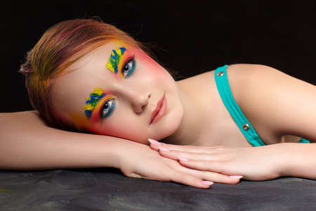 Teenager girl portrait with unusual face art make-up. Paint on brows and hair. Young female is sitting at a black table on black background.