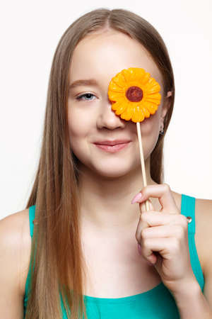 Teenager girl with flower lollipop in hands closing eye and smiling. Sweet tooth concept. 免版税图像