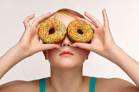 Teenager girl with unusual face art make-up. Child with donuts in hands closing eyes and looking through holes in donuts. Sweet tooth concept.