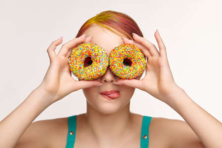 Teenager girl with unusual face art make-up. Child with donuts in hands closing eyes and looking through holes in donuts and showing tongue. Sweet tooth concept.