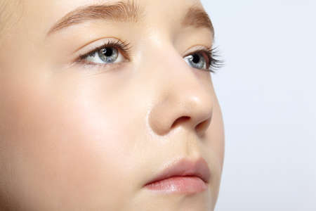 Closeup shot of human teenager girl face. Young female with natural face and eyes beauty makeup.
