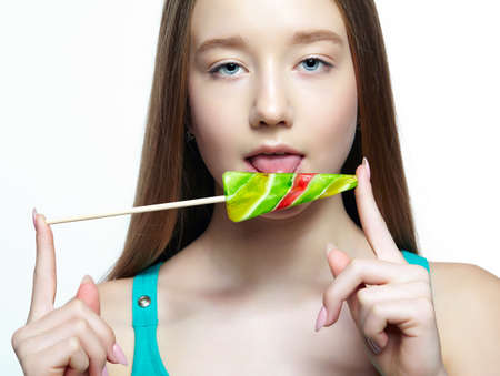 Teenager girl licking the lollipop. Sweet tooth concept. 免版税图像