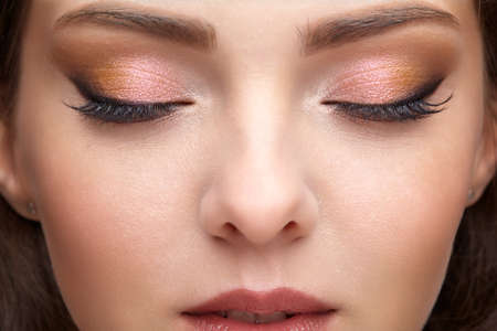 Closeup portrait of female part of face. Human woman with red lips and smoky eyes beauty makeup. Eyes closed Stockfoto
