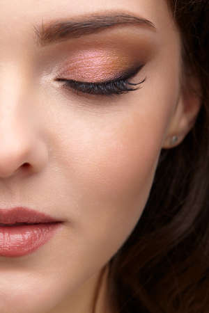 Closeup portrait of female part of face. Human woman with red lips and smoky eyes beauty makeup. Eyes closed