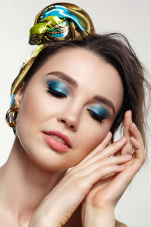 Portrait of young woman on gray background. Female posing in headscarf with hand near face. Makeup with blue eyeshadow and yellow eyeliner.