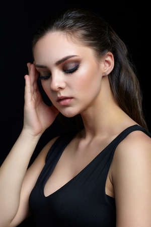 Beauty portrait of young woman with hand near face on black background. Brunette girl with evening female makeup and black dess touches face with fingers. Foto de archivo