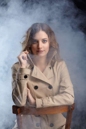 Portrait of young beautiful blonde woman is sitting on a chair. Female in beige cloak on smoke background. Stock fotó