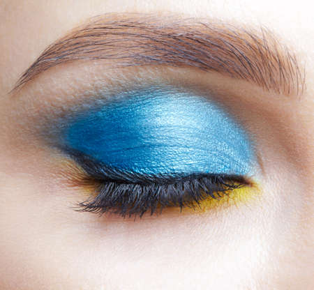 Closeup macro shot of closed human female eye. Woman with natural evening vogue eyes beauty makeup. Eye with blue smoky eyes shadows, black arrow and yellow liner.