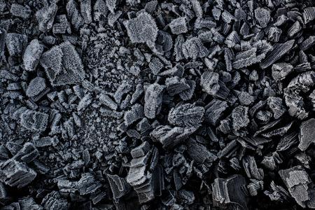black: Black coal in white frost. Stock Photo