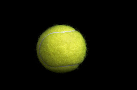 Tennis ball isolated on black background. Stock Photo