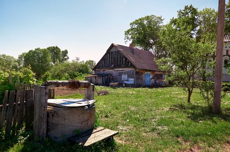 Belarus. The village of Muravank An ancient well near the village wooden hut. May 25, 2017