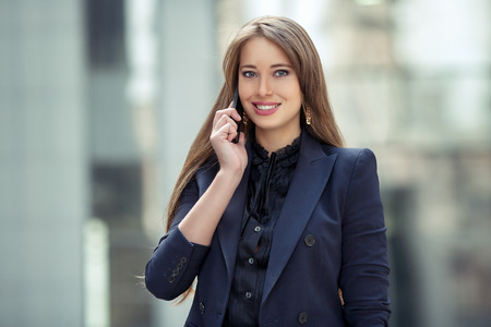 pretty hair: business woman talking on a cell phone on the background of the business center