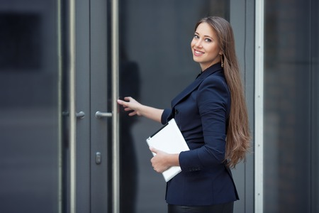 door opening: A beautiful business woman enters the office