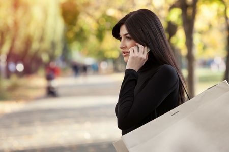 beautiful woman speaks by phone with shopping bag in park