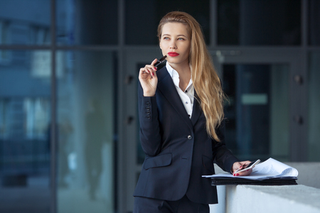 portrait of a business woman with a pen on the background of the business center Stock Photo
