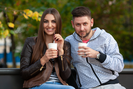 young couple drinking cocktails in the park. Look at the camera